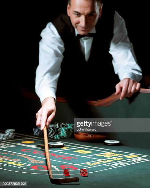 Male croupier leaning on gaming table using rake to retrieve dice