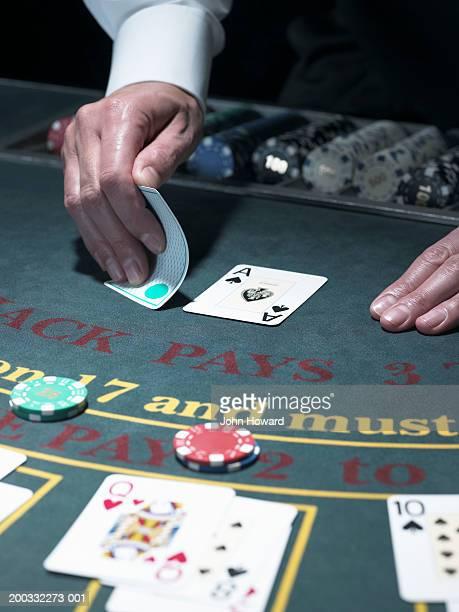Male croupier looking at card at Blackjack table, close-up