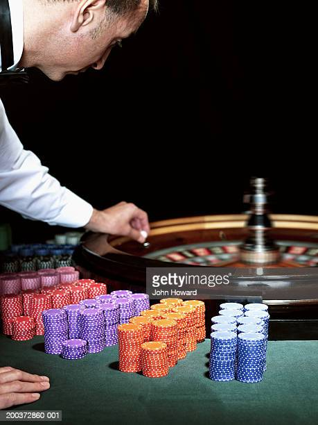Male croupier placing ball on roulette wheel