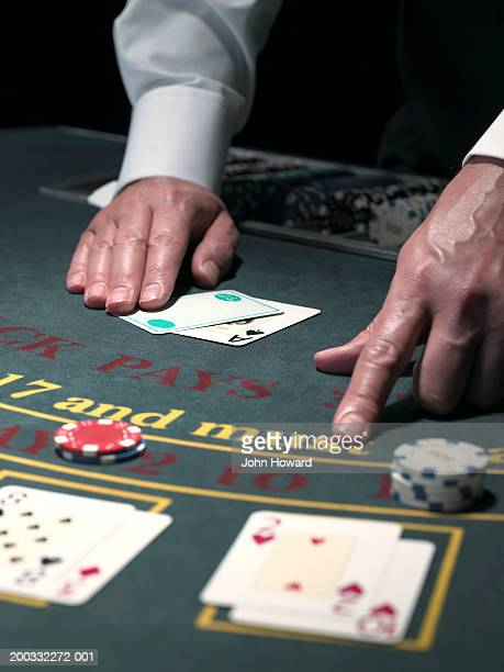 Male croupier pointing to player's hand at table, close-up