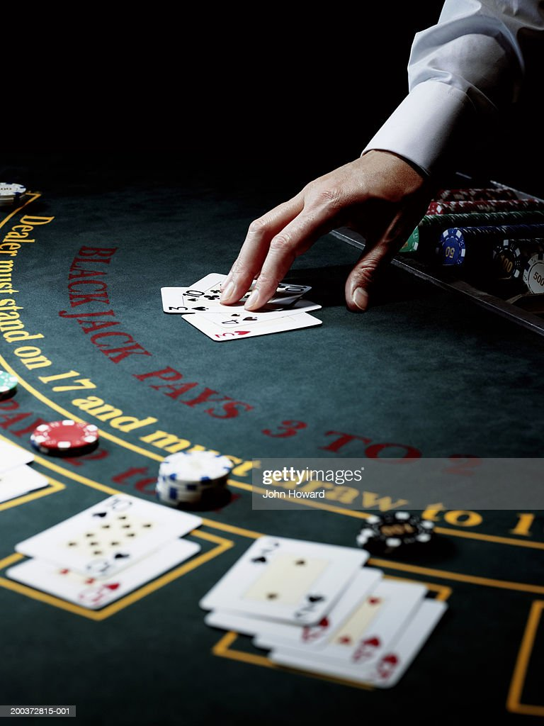 Male croupier resting hand on upturned cards on gaming table : Stock Photo
