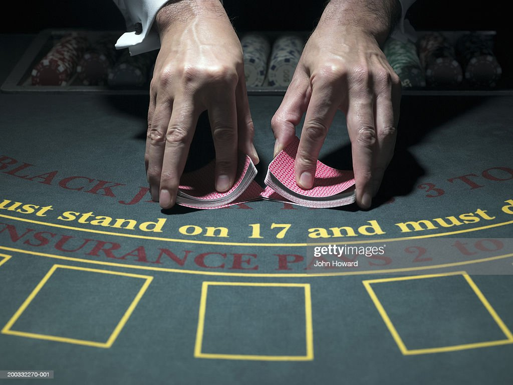 Male croupier shuffling cards at table, merging two piles, close-up : Stock Photo