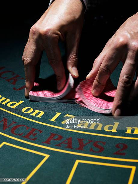 male croupier shuffling cards on gaming table, close-up - shuffling stock photos and pictures