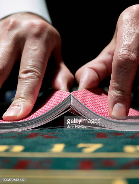 Male croupier shuffling cards on gaming table, close-up
