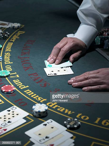 Male croupier turning cards at table, close-up