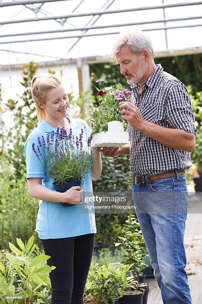 Macho cliente le pide información personal de la planta en centro de jardinería : Foto de stock