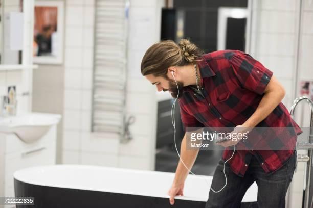 Male customer examining bathtub while shopping in hardware store