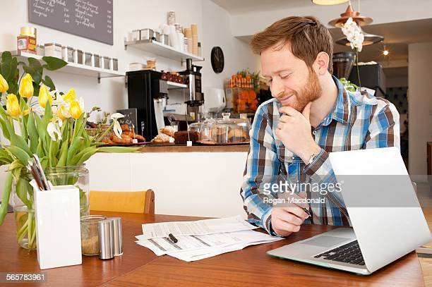Male customer filling in application form in cafe