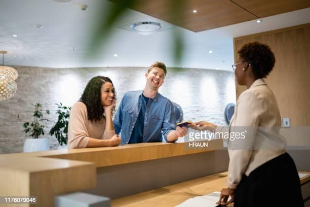 männlicher kunde gibt pass an weibliche managerin - gast stock-fotos und bilder