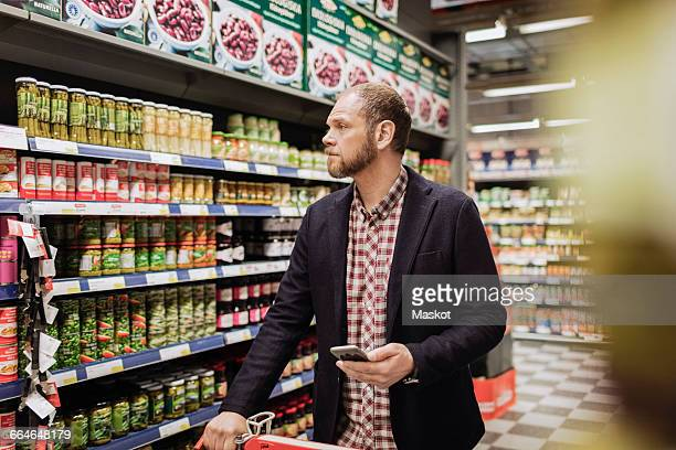 male customer holding smart phone while shopping in grocery store - man shopping stock pictures, royalty-free photos & images