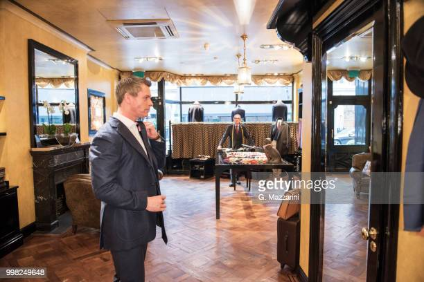 male customer in full suit looking at mirror in tailors shop - custom tailored suit stock pictures, royalty-free photos & images