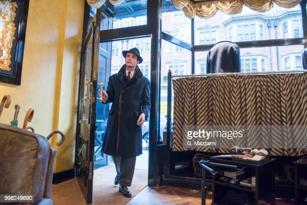male customer in winter coat and trilby arriving in tailors shop - winter coat stock pictures, royalty-free photos & images