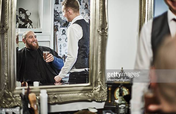 Male customer laughing with barber