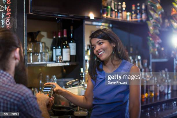 Male customer paying by credit card machine to barmaid in public house