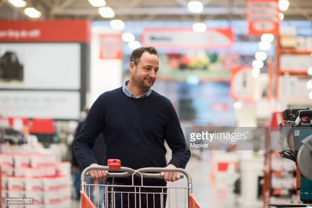 Male customer pushing shopping cart at hardware store
