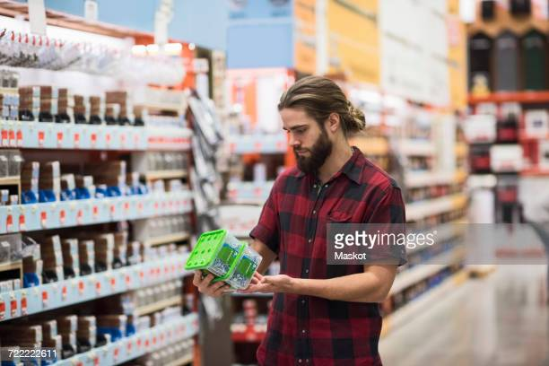 Male customer reading label on nail box in hardware store