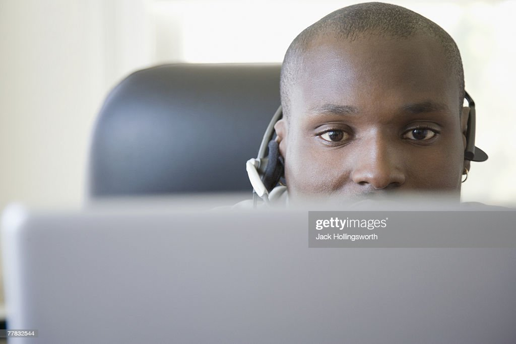 Male customer service representative wearing a headset in front of a laptop : Stock Photo