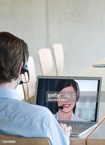 Male customer service representative working on laptop