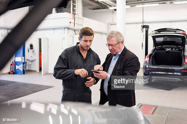 Male customer showing mobile phone to mechanic at auto repair shop