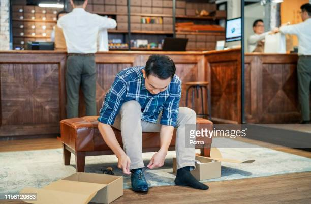 male customer trying on dress shoes in store - mens dress shoes stock pictures, royalty-free photos & images