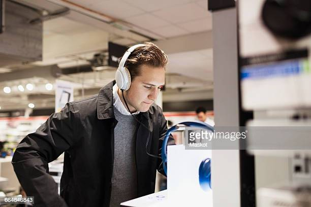Male customer wearing headphones while standing in electronics store