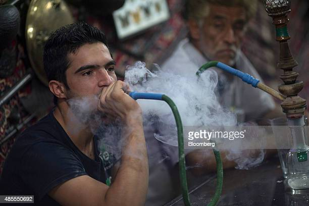 Male customers smoke shisha pipes inside the Haj Mirza traditional teahouse in the Nagshe Jahan bazaar in Isfahan Iran on Thursday Aug 27 2015 Iran...