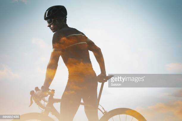 male cyclist and sky, double exposure - multiple exposure sport stock pictures, royalty-free photos & images