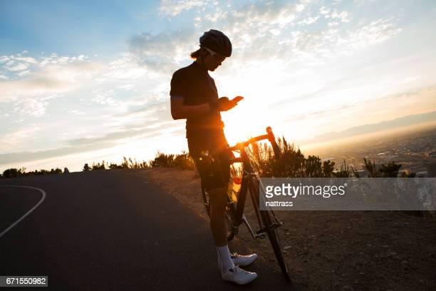 Mannelijke fietser zijn mobiel op een rit van de opleiding controleren