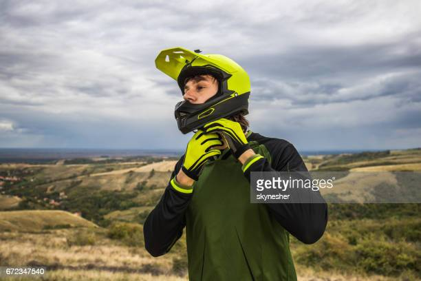 Male cyclist fastening bicycle helmet in nature.