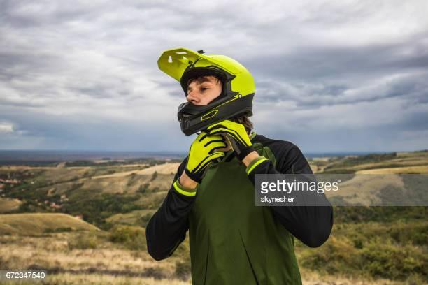 Mannelijke wielrenner fiets helm bevestiging in de natuur.