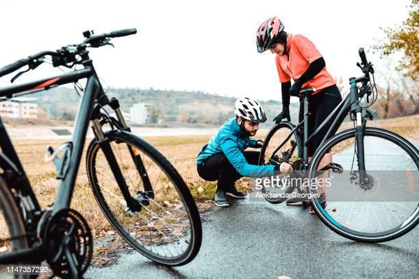 manliga cyklist fast ställande hans flick väns bike chain - partire bildbanksfoton och bilder