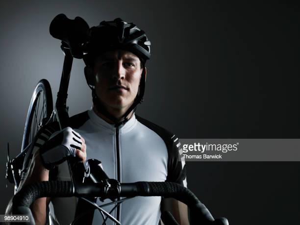 Male cyclist holding bike on shoulder