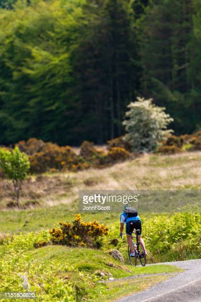 male cyclist on a rural road - johnfscott stock pictures, royalty-free photos & images