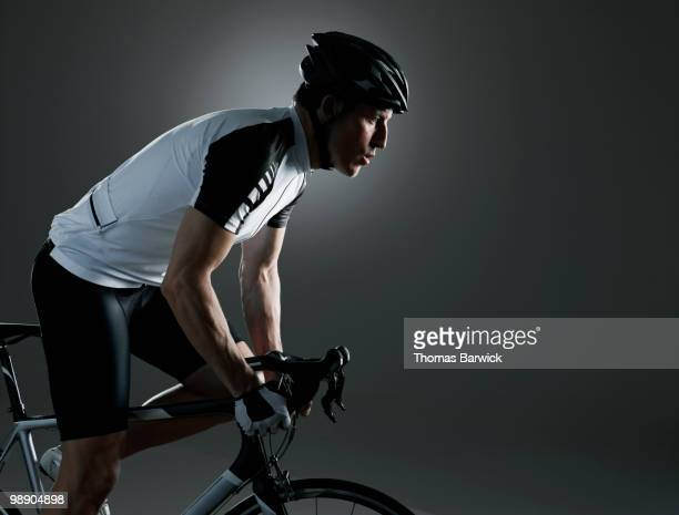 male cyclist peddling bike looking ahead - pedalantrieb stock-fotos und bilder