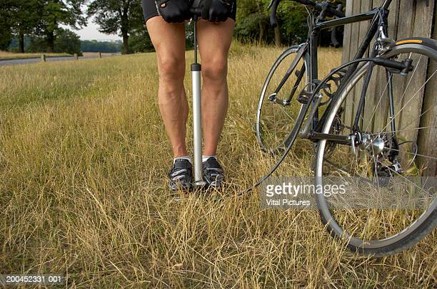male cyclist pumping up bicycle tyre outdoors, low section - air pump stock photos and pictures