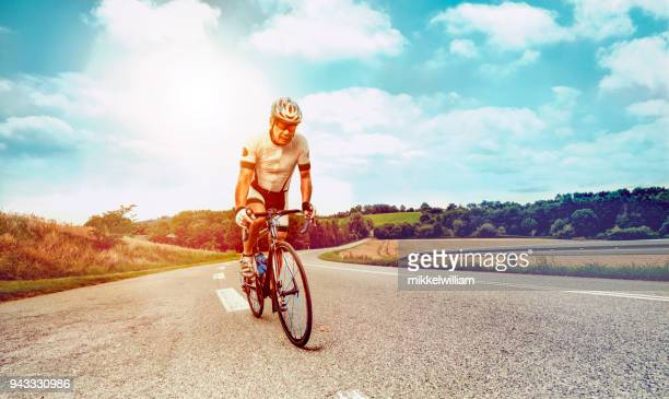 Male cyclist rides professional race bike up a steep hill