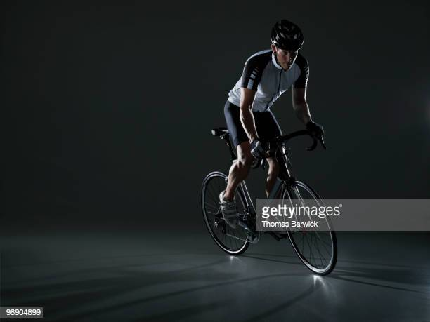 Male cyclist riding bike standing in pedals