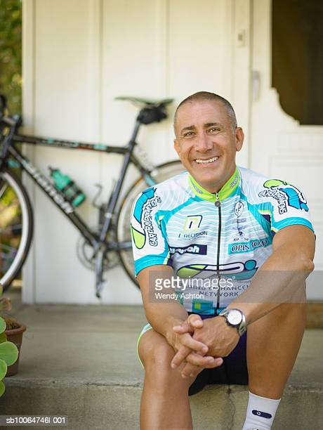 Male cyclist sitting on doorstep, smiling, portrait