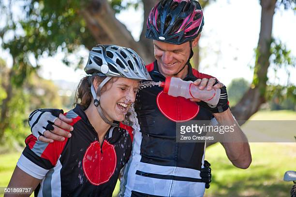 Male cyclist squirting water at woman's face