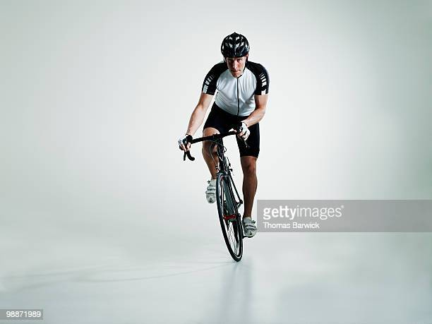 male cyclist standing in pedals riding bike - riding stock pictures, royalty-free photos & images