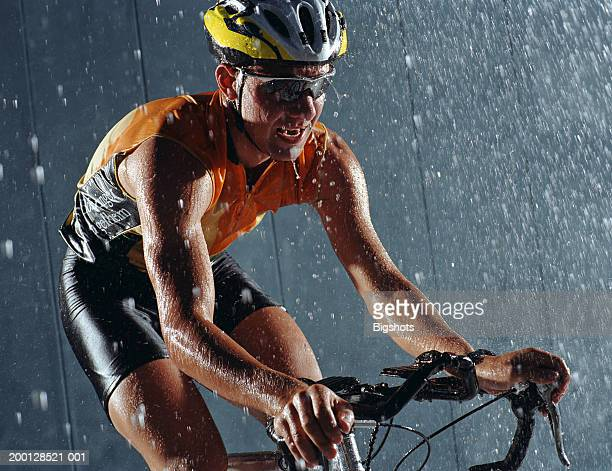 Male cyclist under shower of water