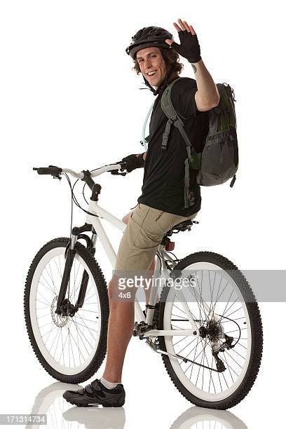 Male cyclist waving his hand