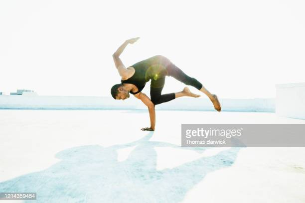 male dancer balancing body on one hand while performing on rooftop - control stock pictures, royalty-free photos & images