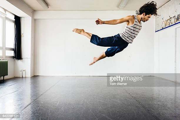 male dancer jumping during a rehearsal - danza moderna foto e immagini stock
