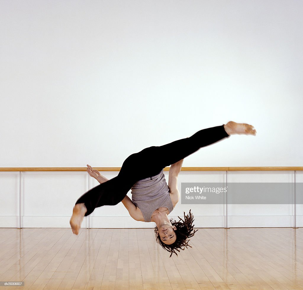 Male Dancer Jumping Upside Down in Mid Air : Stock Photo