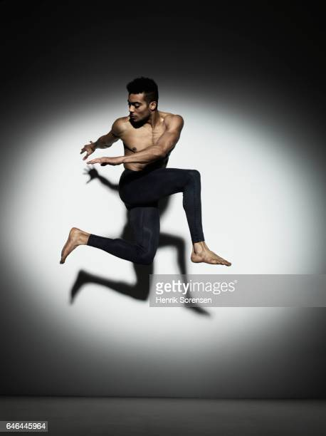 Male dancer leaping through a spotlight