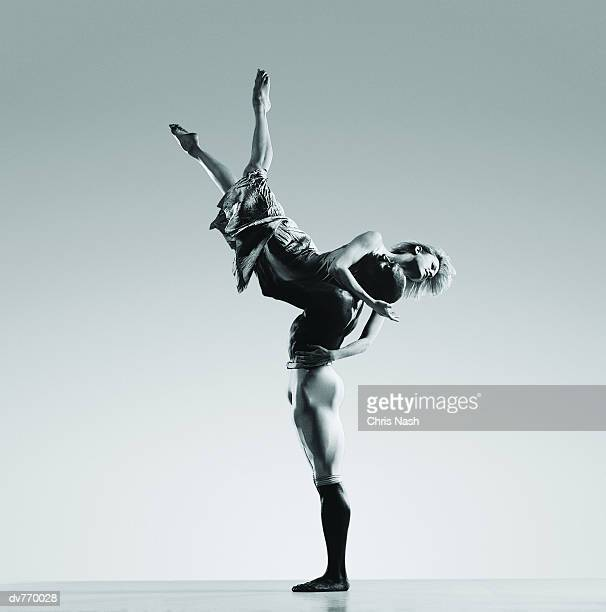 male dancer supporting female dancer in mid air - male ballet dancer stock photos and pictures