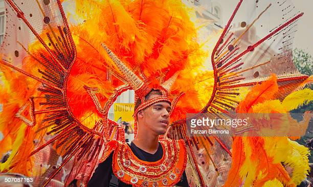 Male dancer with bright plumage dances for the crowd at the Notting Hill Carnival.