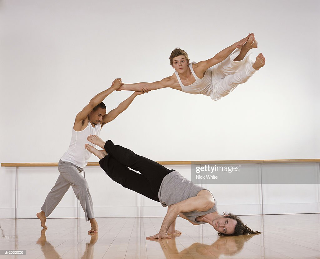 Male Dancers Supporting on Another Male Dancer With His Arms Raised : Stock Photo