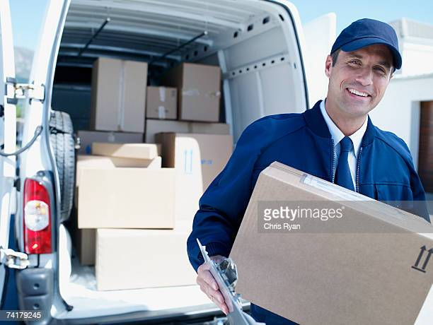 Male delivery person in cap with van and boxes